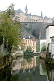 River of Alzette and town wall in Luxembourg City. Mirroring houses in the river of Alzette in Luxembourg-Ground against the background of the foggy uptown of Stock Image