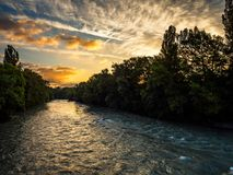 River Arve, Switzerland, in deep shadow as the sky is illuminated by the rising sun. royalty free stock image