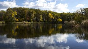 A river with autumn trees and beautiful clouds. Travels. Fishing. A river with autumn trees and beautiful clouds. Recreation. Travels. Fishing Stock Photo