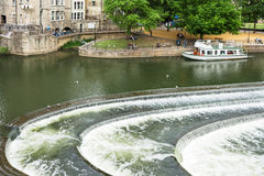River Avon with weir and tour boat in Bath. England. The river Avon with weir and tour boat in Bath. People relaxing in the park near the Pulteney Bridge Stock Photography