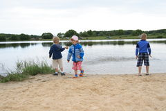 On the river bank. Children plays on the bank in summer Royalty Free Stock Image