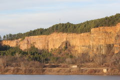 Arkansas River bank during sunset Little Rock. River bank during winter sunset. A bluff with pine forest can be seen from the other side of the river. Arkansas Stock Photo