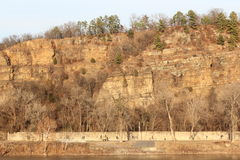 Arkansas River bank during sunset Little Rock. River bank during winter sunset. A bluff with pine trees can be seen from the other side of the river. Arkansas Stock Photo