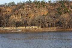 Arkansas River bank during sunset Little Rock. River bank during winter sunset. A bluff with pine trees can be seen from the other side of the river. Arkansas Stock Photography