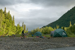 River bank tent campsite in wild, remote Alaska. A campsite and tents beside a river in wild, remote Alaska under a cloudy, stormy sky Royalty Free Stock Photo