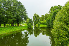 The river banks are covered with green grass and green trees in Stock Image