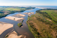 River Banks Ocean Cane Air. Air Photo image overlooking a large river with its sand banks,beach coastline and the farming landscape of sugar cane fields going Royalty Free Stock Photo