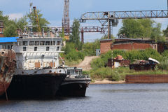 River bay with rusty cargo ships on sunny day Stock Photos
