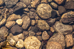 River Bed - Stones beneath the clear water of a river Stock Photo