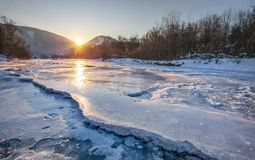 River Bela completely frozen during extreme cold. Early morning sun rising behind mountains reflected in ice layer with snow patches. Liptovsky Hradok Royalty Free Stock Photos