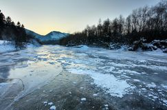 River Bela completely frozen during extreme cold. Early morning sun reflected in ice layer covered with snow patches. Liptovsky Hradok, Slovakia Stock Photo