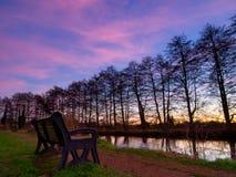 River Bench at Sunset. Riverside Park Bench at sunset Stock Photo