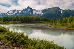 River Bend Below Snow Capped Mountain Scene. On a sunny alaska day Royalty Free Stock Photography