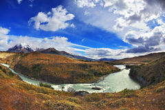 The river bends a horseshoe under the flying clouds. Travel to Chile. The river bends a horseshoe under the flying clouds. The picture was taken Fisheye lens Royalty Free Stock Images