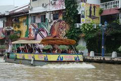 River boat in Melaka. A river boat along the river Melaka, Malaysia. Cool and unique grafitti on the buildings Stock Images