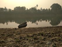 A river boat on the river bank. An isolated river boat on the river bank royalty free stock images