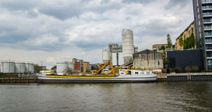 A river boat being loaded with sand in an industrial area in West London Royalty Free Stock Image