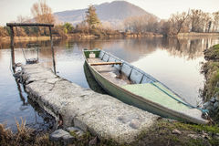 River boat. A green long boat anchored near the banks of a river royalty free stock photography