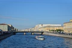 River boat sails under Semenovsky bridge over the Fontanka river Stock Photography