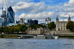 River boat on the river thames. A sightseeing river boat sailing by the tower of London on the thames river in London England UK stock images