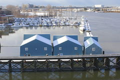 River Boathouses. A row of boathouses used for storing and protecting boats sits on a river Stock Photo