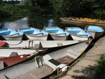 River Boats. A collection of rowing boats and punts resting on a river in England Stock Photos