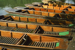 River Boats for Hire. Punts awaiting punters on the backs of the river Cam on a summer's afternoon in Cambridge UK Royalty Free Stock Photo