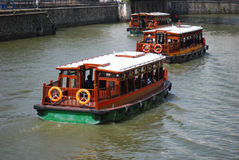 River Boats. Some boats ferrying tourists along a shallow calm river within an Asian city Royalty Free Stock Image