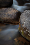 River Boulders. A detailed view of a river flowing around mossy boulders Stock Image