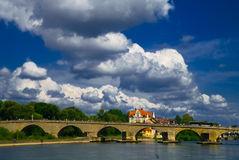River bridge. A stone bridge with many arches over a river in Regensburg, Germany under a beautiful blue sky with white clouds royalty free stock photo