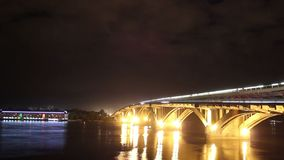 River bridge at night, cars drive water flows, clouds time-lapse stock video