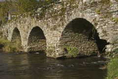 River and bridge. Old bridge with arches and fast flowing river in the ardennen royalty free stock photography