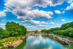 River and bridge in Paris, France on sunny day. On cloudy blue sky background. Ships on water. Green trees on banks. Landmark and tourist destination. Summer Stock Photography