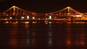 River bridge traffic at night, shining reflections, ferry boats. Stock footage stock video footage