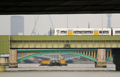 River bridges. Thames group of bridges, crossing train and tag boat Royalty Free Stock Images