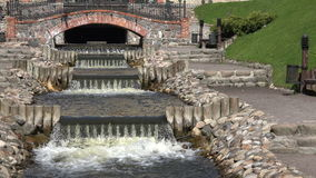 River brook waterfall water stairs flow between park path. 4K stock video