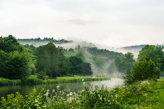A river with calm water and trees reflections covered by mist. River with calm water and trees reflections covered by mist stock photography