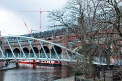 River canal with bridges in Manchester. MANCHESTER, UNITED KINGDOM - 5 March, 2016: A view of river canal in the city of Manchester with bridges, boats and tower Royalty Free Stock Image