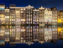 River, canals and traditional old houses Amsterdam. Amstel river, canals and reflection of buildings on water at evening Amsterdam, Netherlands Royalty Free Stock Photography