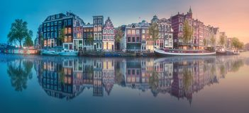 River, canals and traditional old houses Amsterdam. Amstel river, canals and sunrise over beautiful Amsterdam city. Netherlands stock photography