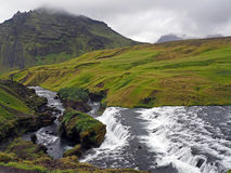 River cascade  in green grass and mossed stones Stock Photo