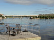 River with chairs and bridge. River chairs bridge railings sky blue table nature resort holiday clouds water Stock Photos