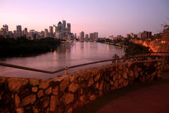 River City. The Brisbane River in Australia at night with a rock wall in the foreground Royalty Free Stock Photography