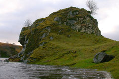 River and Cliff. A swollen river rushing past a rugged scottish cliff Royalty Free Stock Images