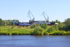 River coast line with grass, ships and cranes for loading Stock Images