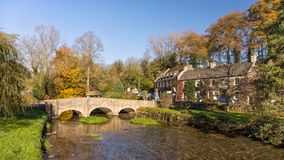The River Coln and Bridge, Bibury, Gloucestershire, England. The River Coln in autumn as it flows under the road bridge in the famous picturesque Cotswold Royalty Free Stock Image