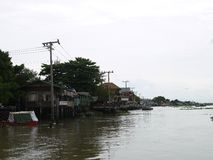 Chaophya river ecology life in the bright sunshine day, community of waterside wooden houses, temples, and parking boats. royalty free stock photo