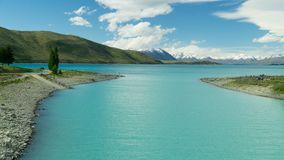 River connected with incredibly blue lake Te Kapo, New Zealand. Lake Te Kapo is breathtaking place. In the background there are Southern Alps with peaks coverd stock photo