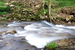 River in countryside. Scenic view of river with small waterfall in countryside with slow motion blur stock photos
