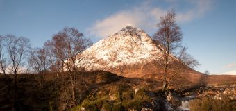 At river Coupall at delta to river Etive. Snowy cone of mountain Stob Dearg 1021 metres high. Stock Images